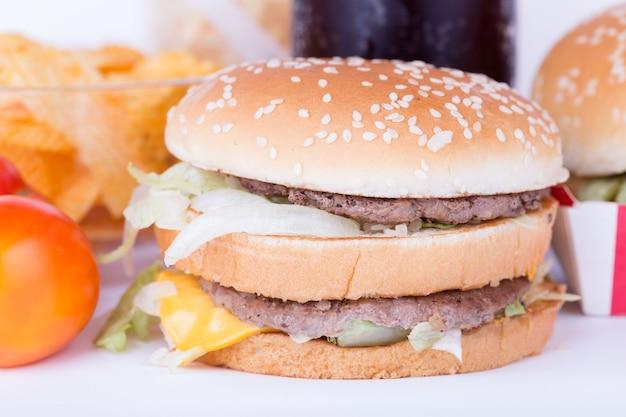 Duży hamburger z warzywami i frytkami.