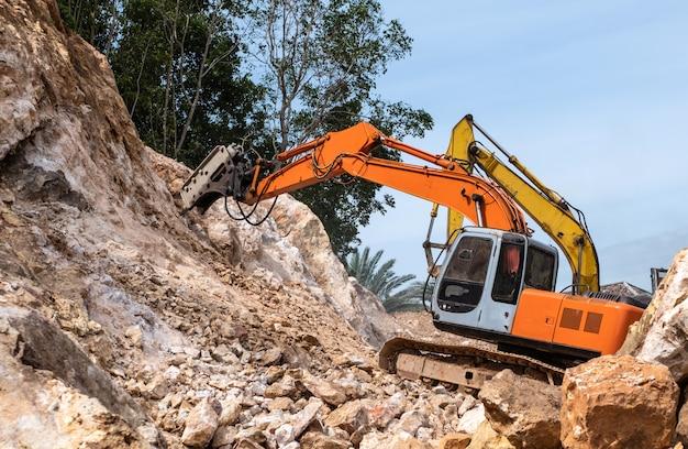 Duży hydrauliczny młot pneumatyczny pracujący na roztrzaskanej skale.