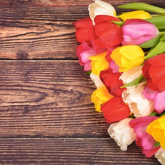 Duży jasny bukiet różnokolorowych tulipanów na deskach w kolorze ciemnobrązowym.