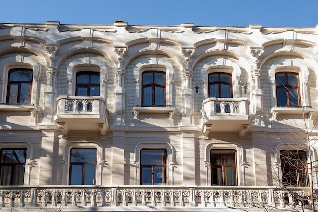 Duży kamienny budynek z wieloma oknami. stary dom o klasycznej architekturze z wieloma łukowymi oknami i balkonami. piękna fasada pałacu