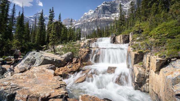 Duży kaskadowy wodospad w środowisku alpejskim z górami w tle park narodowy banffkanada