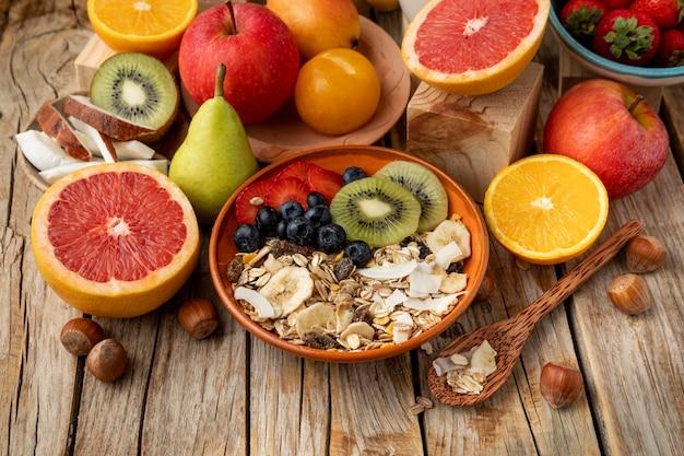 Duży kąt asortymentu owoców z płatkami śniadaniowymi i łyżką
