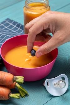 Duży kąt jedzenia dla niemowląt w misce z marchewką i smoczkiem