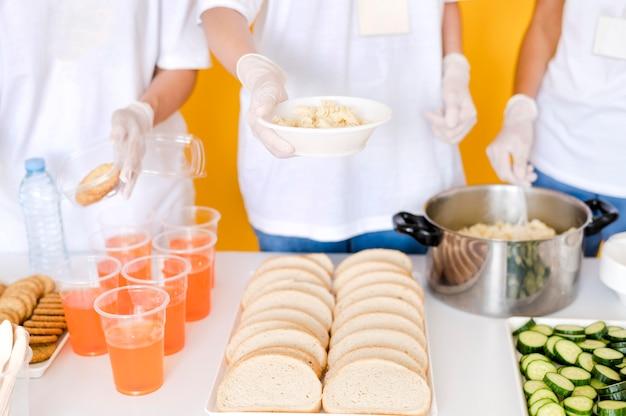 Duży kąt ludzi przygotowujących jedzenie do darowizny