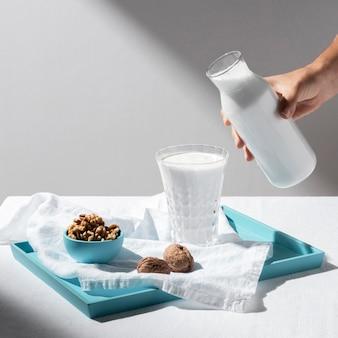 Duży kąt osoby nalewającej mleko do pełnej szklanki z orzechami włoskimi na tacy