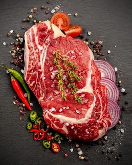 Duży kawałek mięsa na kości leży na drewnianej desce z przyprawami i świeżymi ziołami
