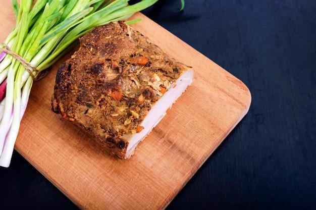 Duży kawałek pieczona szynka wieprzowa, z zieloną cebulą na desce do krojenia na ciemnym tle.