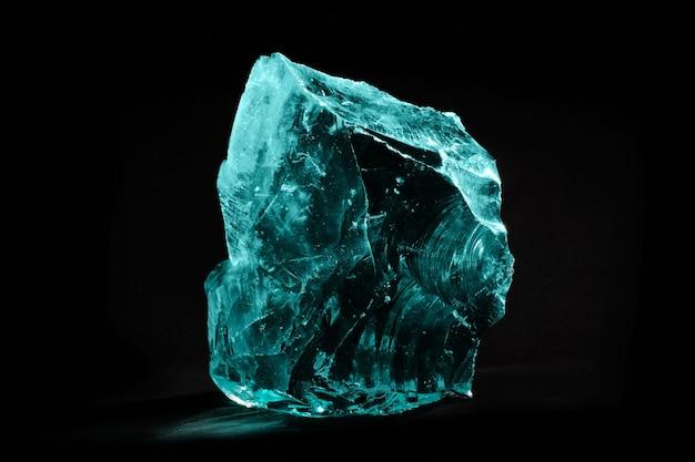 Duży kawałek potłuczonego niebieskiego szkła na ciemnym tle