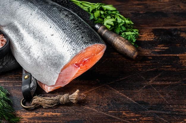 Duży kawałek surowego łososia cięte na drewnianej desce do krojenia z nożem szefa kuchni. ciemne tło drewniane.