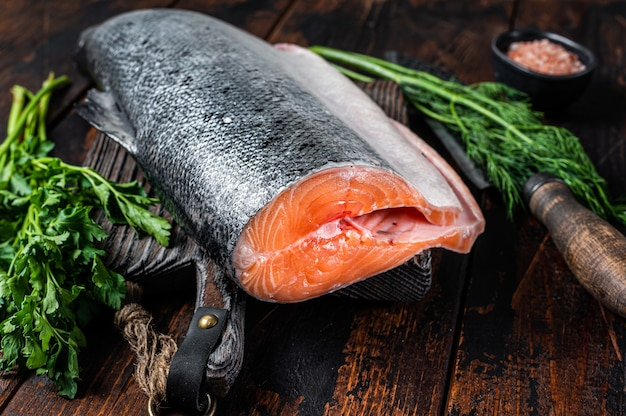Duży kawałek surowego łososia cięte na drewnianej desce do krojenia z nożem szefa kuchni