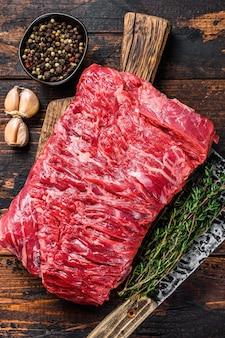 Duży kawałek surowego mięsa pokrojonego na mostek wołowy z ziołami i tasakiem rzeźniczym. ciemne drewniane tło. widok z góry.