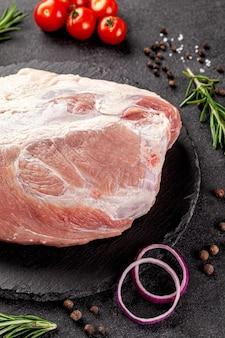 Duży kawałek surowego mięsa wieprzowego, biodra lub polędwicy na czarnym tle