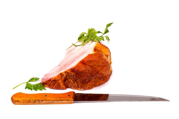 Duży kawałek świeżej szynki wieprzowej i nóż kuchenny na białym tle