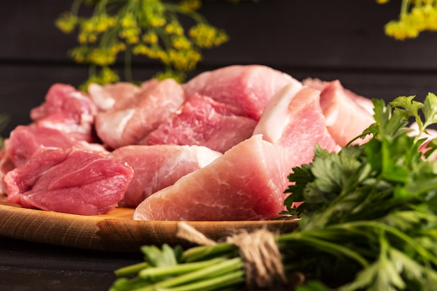 Duży kawałek wołowiny na pokładzie. czarne tło, natka pietruszki. zdjęcie do przepisu kulinarnego