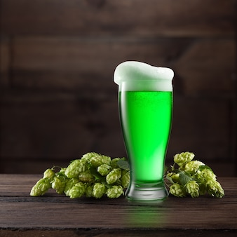 Duży kieliszek jasnozielonego piwa z gałązką dojrzałego naturalnego organicznego chmielu na drewnianym stole. koncepcja happy st patrick's day.