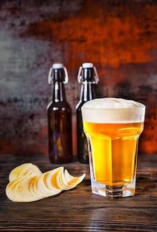 Duży kieliszek świeżo nalanego jasnego piwa na dwie butelki piwa obok chipsów na ciemnym drewnianym biurku. koncepcja żywności i napojów
