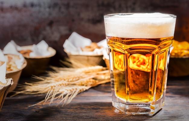 Duży kieliszek świeżo nalewanego piwa przy talerzach z pistacjami, małymi preclami i orzeszkami ziemnymi na ciemnym drewnianym biurku. koncepcja żywności i napojów