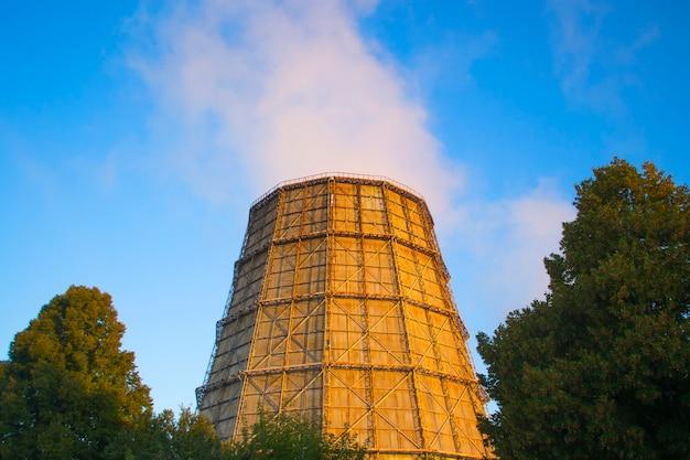 Duży komin elektrociepłowni o wschodzie słońca, zachodzie słońca z czystym, błękitnym niebem z dymem z komina