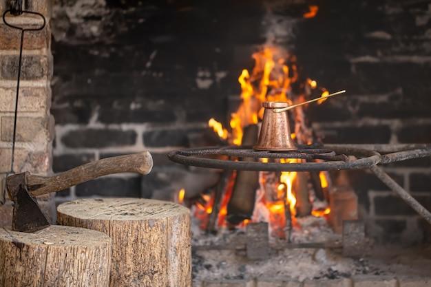 Duży kominek z płonącym ogniem i turkiem w którym parzona jest kawa.