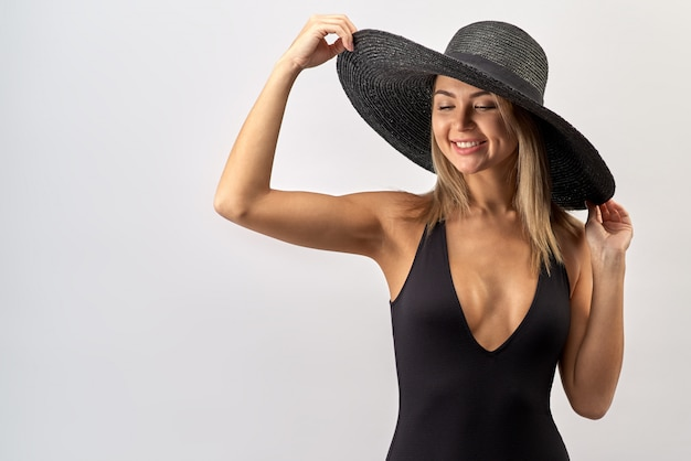 Duży kontrast portret studyjny atrakcyjnej kobiety rasy białej o długich blond włosach w czarnym bikini i kapeluszu z dużym uśmiechem zębów