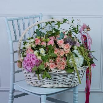 Duży kosz mieszani kwiaty stoi na białym krześle