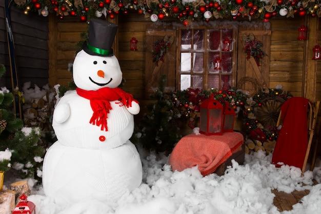 Duży kryty bałwan zimowy na zdobionym drewnianym domku z bawełny snow on the floor.