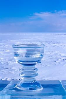 Duży kubek lodu z lodem na tle śniegu i błękitnego nieba. na lodowym cokole stoi piękna miska na lód. pęknięcia i rysy na lodzie. na niebie są chmury. pionowy.