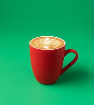 Duży kubek sztuki latte kawy mlecznej na zielonym tle, koncepcja pionowa, minimalna.