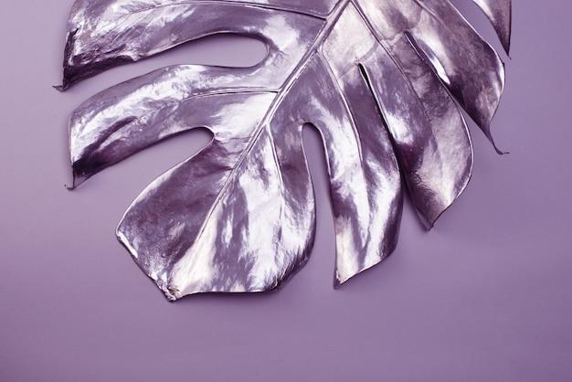 Duży liść monstery malowany w kolorze srebrnym na szarym tle. minimalistyczna koncepcja luksusu. dobry na plakat do dekoracji wnętrz.