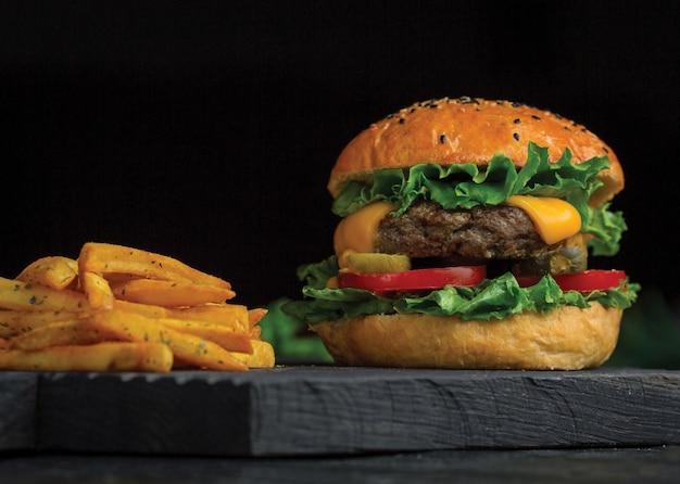 Duży mac burger i frytki na desce z ciemnego drewna.