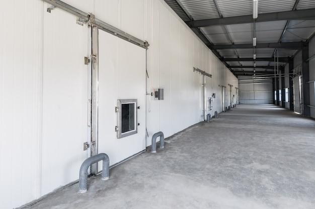 Duży magazyn mroźni w zakładzie. fasada z przemysłowymi drzwiami magazynowymi mroźni