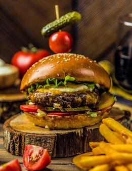 Duży max burger stojący na kawałku drewna