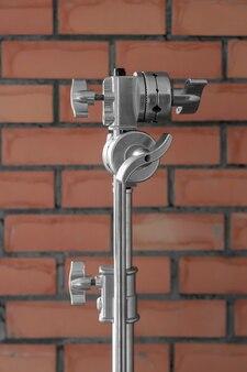Duży metalowy statyw oświetleniowy z mechanizmem mocującym nad murem z czerwonej cegły
