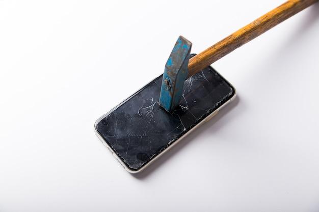 Duży młotek z drewnianym uchwytem łamie smartfon