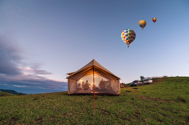 Duży namiot z kempingami turystów świecącymi na zielonym wzgórzu i balonami na ogrzane powietrze latającymi na wieczornym niebie na wsi