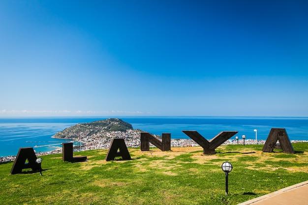 Duży napis alanya, z panoramicznym widokiem z góry na miejscowość wypoczynkową ze wzgórzem, zamkiem i wybrzeżem morskim