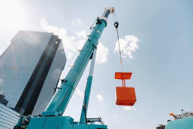 Duży niebieski dźwig samochodowy jest gotowy do pracy na placu w pobliżu dużego nowoczesnego budynku. największy dźwig samochodowy z żółtą kołyską do rozwiązywania skomplikowanych zadań.