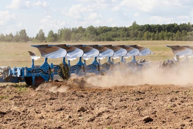 Duży niebieski pług orze glebę na polu, z pługa wylatuje dużo pyłu z suchej gleby