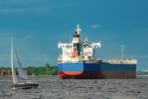 Duży niebieski statek towarowy przemieszcza się do portu w rydze