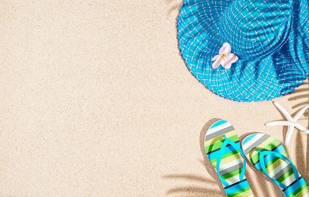 Duży okrągły niebieski kapelusz na lato i kolorowe sandały w paski na piasku z cieniem palmy, widok z tp, miejsce na kopię