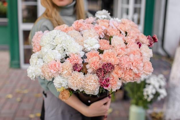 Duży piękny bukiet mieszanych kwiatów w ręce kobiety.
