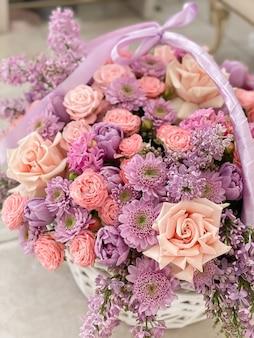 Duży piękny kosz w delikatne różowe kwiaty. chryzantemy, róże, bzy, tulipany, hiacynty. romantyczny prezent na święta. obraz tła kwiaciarni