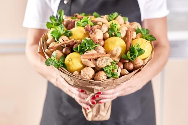 Duży piękny owocowy bukiet cytryn, orzechów, imbiru i mięty w rękach kobiecej kwiaciarni