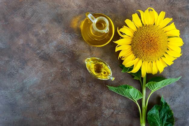 Duży piękny słonecznik i butelka olej na rocznika tle. rolnictwo do produkcji ropy. jesieni tło z słonecznikiem. wolne miejsce na twój projekt.