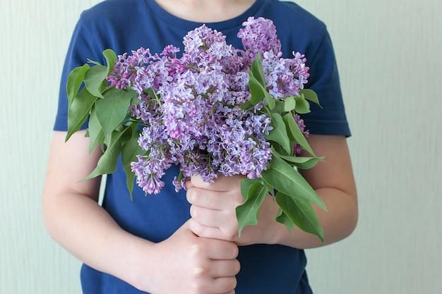 Duży piękny wiosenny bukiet bzów w ręce kobiety.