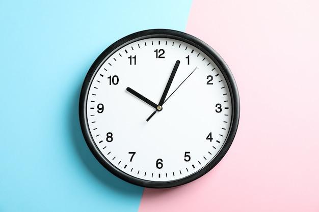 Duży piękny zegar biurowy na dwukolorowym jednolitym kolorze różowym i jasnoniebieskim