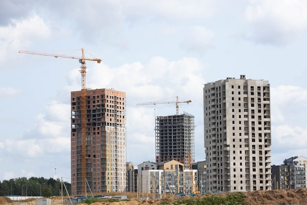 Duży plac budowy z rusztowaniem, żółtym żurawiem wieżowym i niebem.