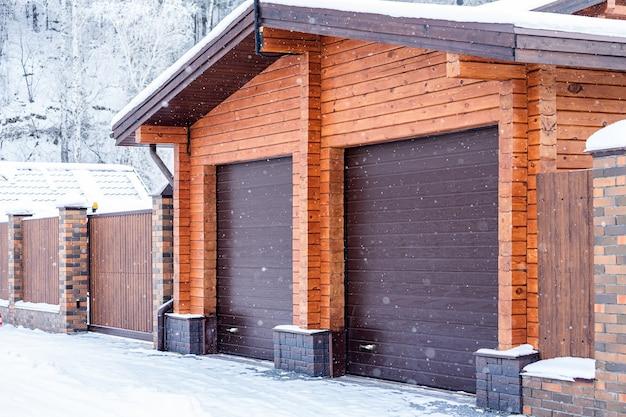 Duży plan lekkiego ceglanego garażu na dwa samochody z automatycznymi bramami w zimowej wiosce