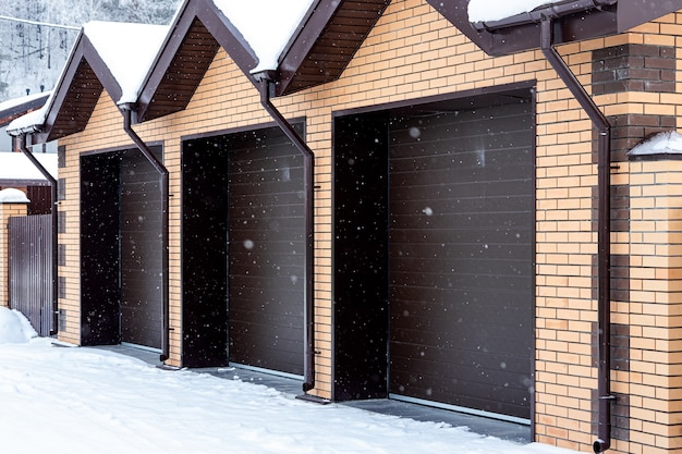 Duży plan lekkiego ceglanego garażu na trzy samochody z automatycznymi bramami w zimowej wiosce