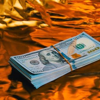 Duży plik dolarów na złotej ścianie.